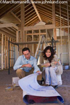 Photo of a Hispanic couple looking at blue prints in a new home being built with exposed studs and two by fours.